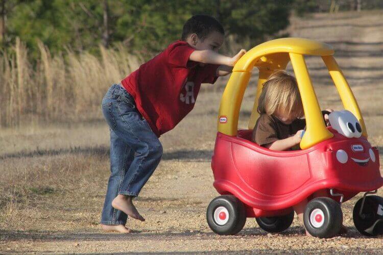 おもちゃの車を押す少年