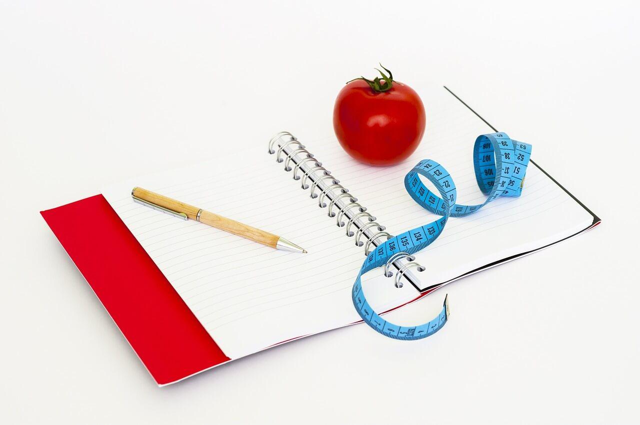 体重を記録するノート、メジャー、食事