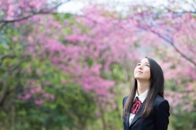 制服を着た女子高生と桜